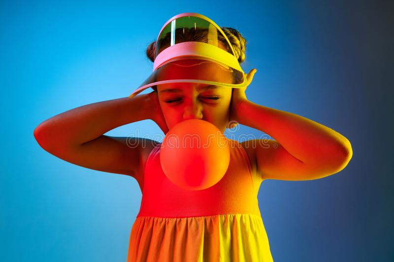 Young girl blowing bubble gum. Happy teen girl standing over trendy blue neon studio background. Beautiful female portrait. Young satisfy girl. Human emotions royalty free stock photo