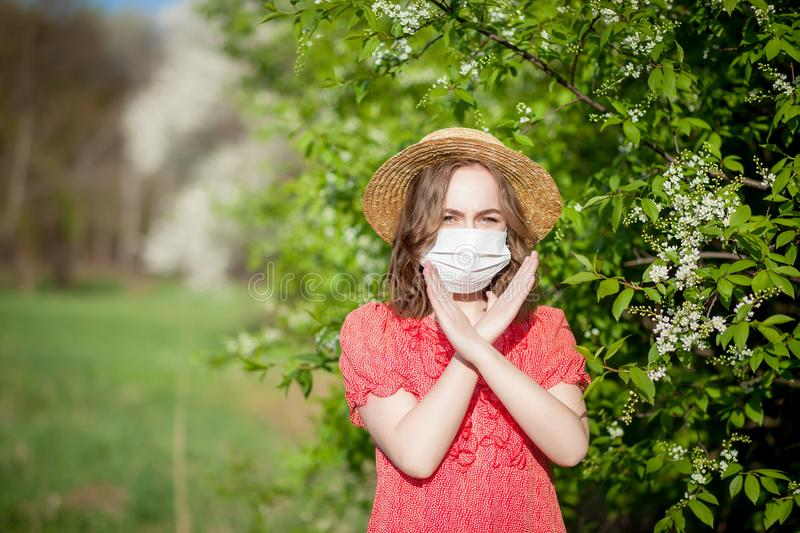 Young girl blowing nose and sneezing in tissue in front of blooming tree. Seasonal allergens affecting people. Beautiful. Lady has rhinitis stock photos