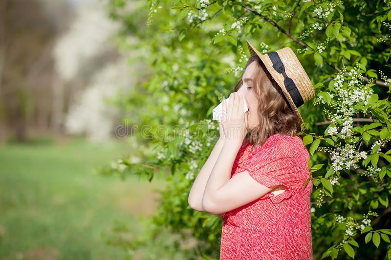 Young girl blowing nose and sneezing in tissue in front of blooming tree. Seasonal allergens affecting people. Beautiful. Lady has rhinitis stock image