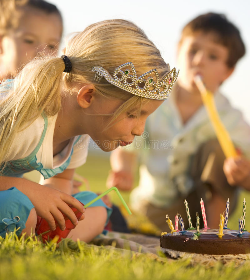A young girl blowing out the candles on her birthday cake stock photo
