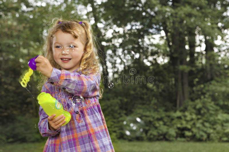 Young girl blowing soap bubbles. At the park royalty free stock photo