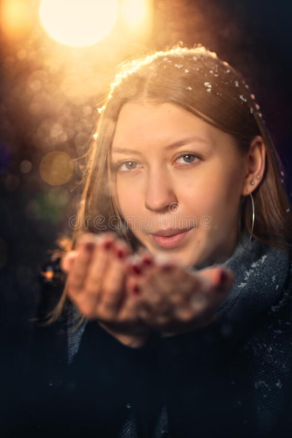 Young girl blows snow on a cold night. Young girl blows snow on a cold winter night royalty free stock photography