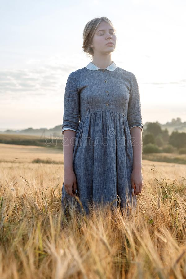 young girl in blue dress with collected hair posing with her eyes closed in field at sunrise. Foggy dawn in background royalty free stock photo