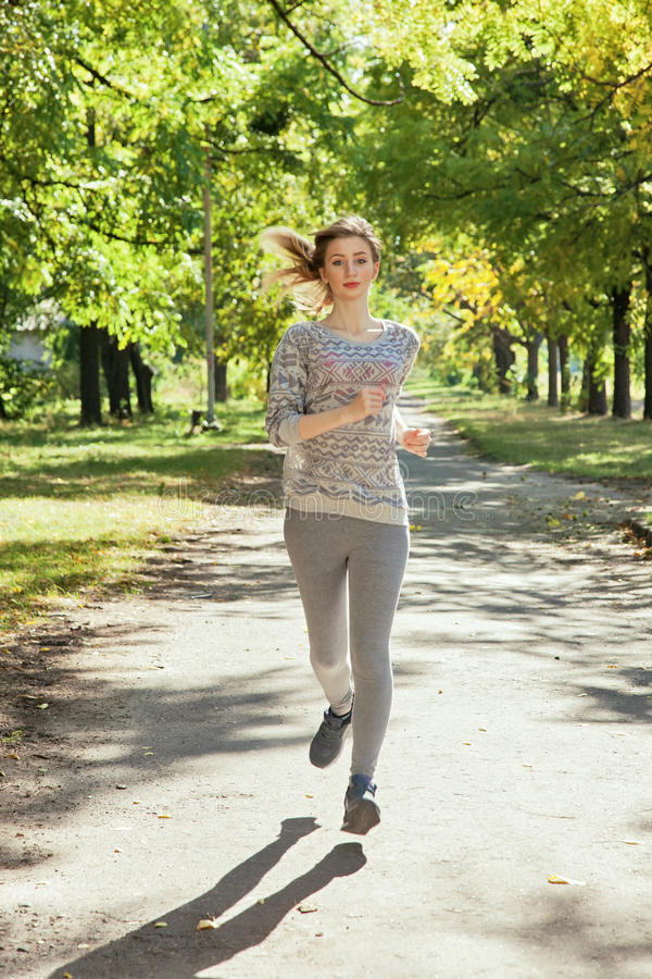 Young girl with blue eyes a joging in the park. Young girl with blue eyes joging in the park. Autumn weather, yellow foliage royalty free stock photography