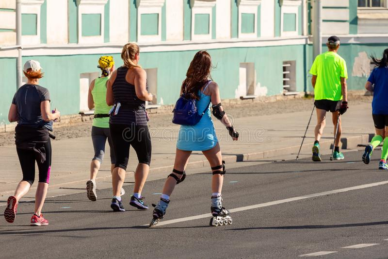 Young girl in a blue short dress on rollers rides along the street during a marathon next to the runners. ST. PETERSBURG, RUSSIA - June 30, 2019: young girl in a stock photo