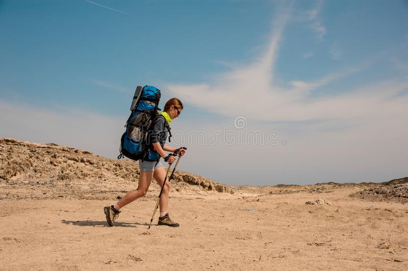 Young girl hiking with walking sticks in desert. Young girl with blue travel backpack hiking with walking sticks in desert stock photography