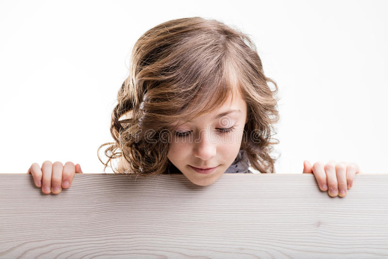 Young girl with board looking down. Young blond haired girl holding painted wooden board looking down stock photo