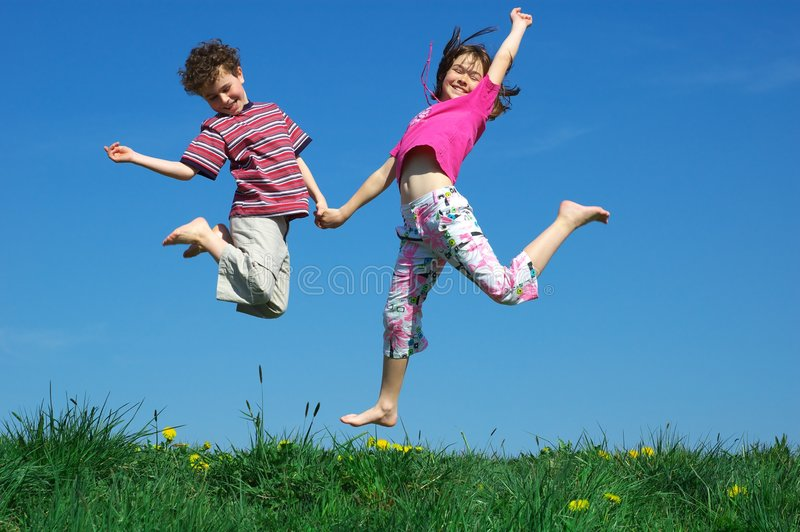 Young girl and boy jumping stock photo