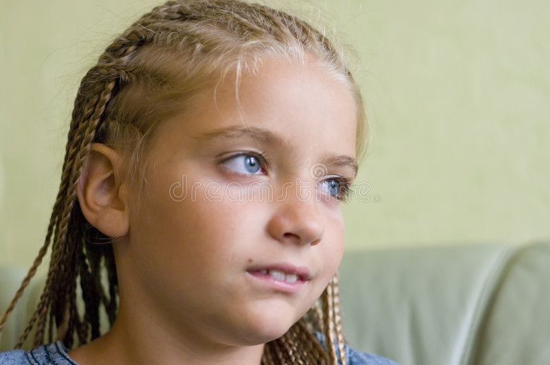 Young girl in braids. Portrait of a young blue eyed girl with braids, looking away stock photo