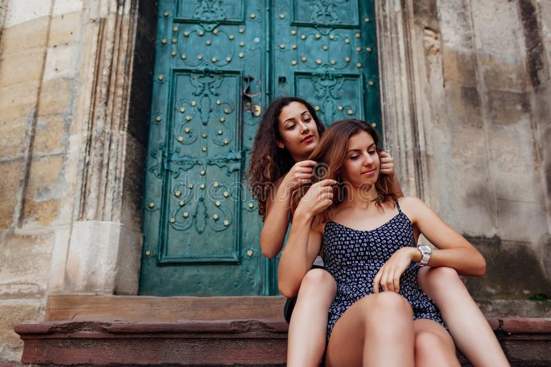 Young girl braids her best friend`s hair sitting on stairs outdoors. Happy women having fun. Spending time together stock images