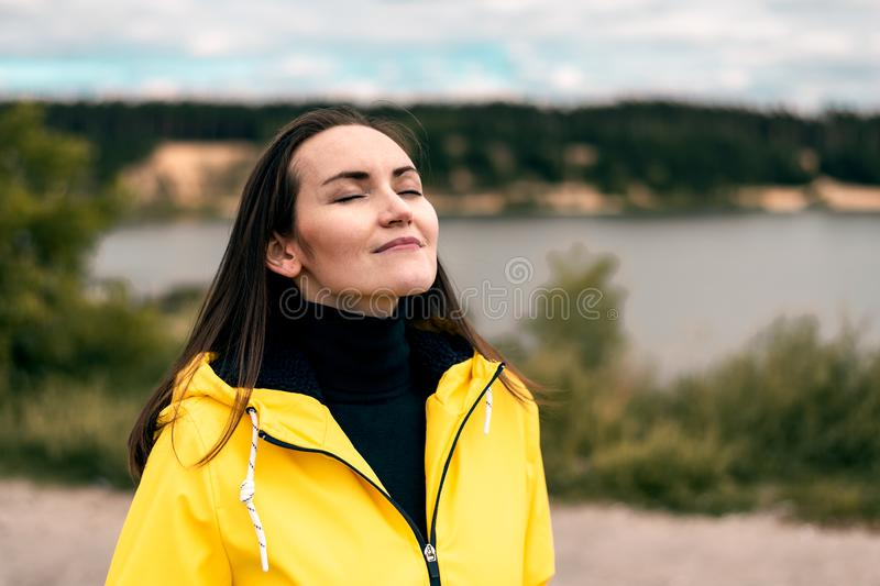 Young girl breathes clean fresh cool autumn air in nature near forest lake in yellow raincoat with a copy space stock photo