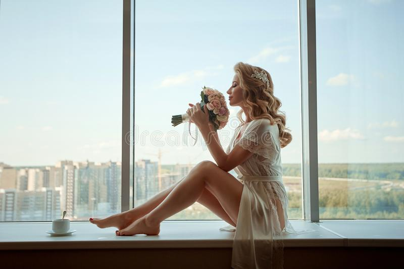 A young girl bride in peignoir sitting on the windowsill with a bouquet. Wedding morning preparation stock photos