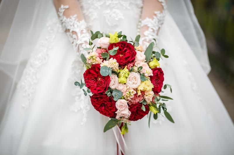 Young girl bride in stay on city street and waits for the groom with bouquet of red and white roses stock photos