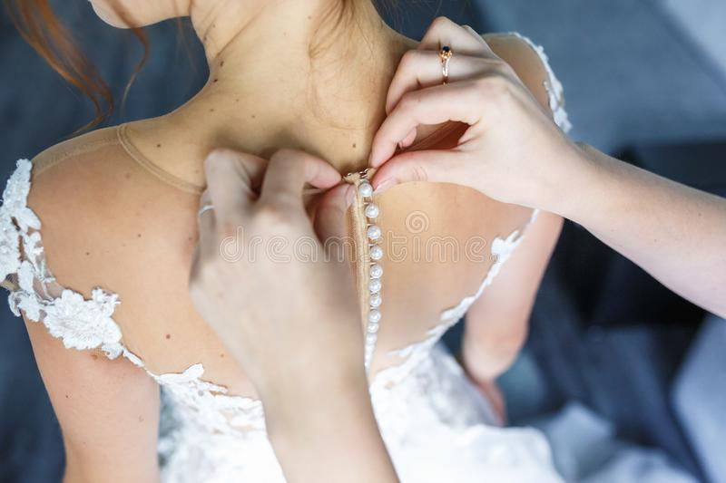 Young girl bride in wedding dress is waiting for the groom. girlfriend helps to fasten a dress stock photos
