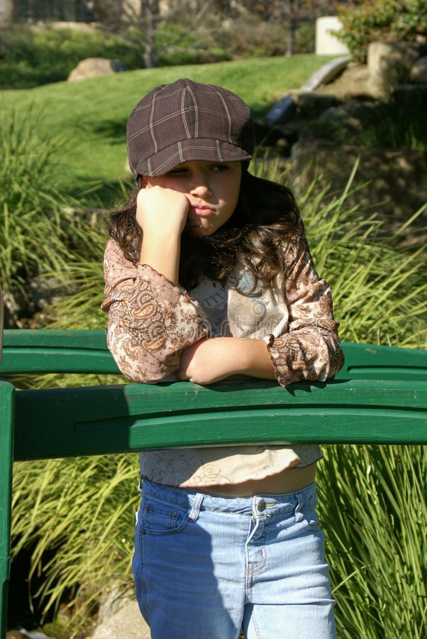 Young girl on a bridge pouting royalty free stock photo