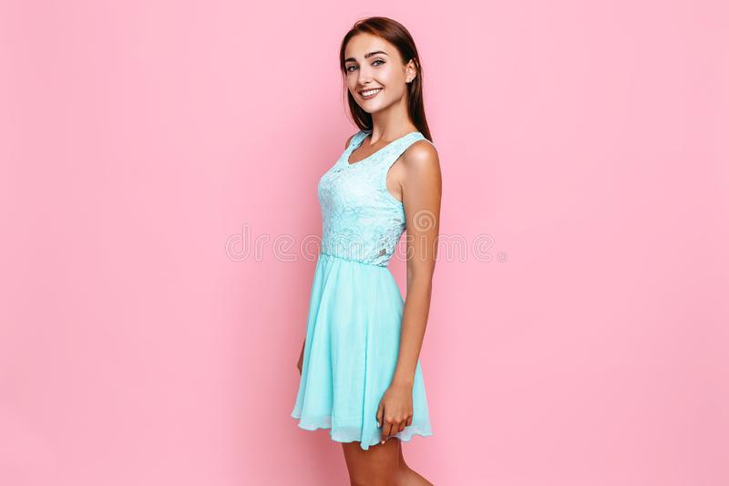 Young girl, in a bright dress, smiling and posing on a pink background. Beautiful young girl, in a bright dress, smiling and posing on a pink background royalty free stock image
