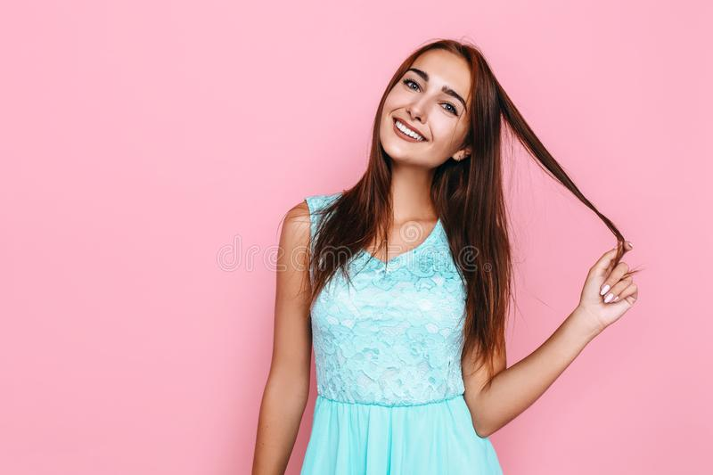 Young girl, in a bright dress, smiling and posing on a pink background. Beautiful young girl, in a bright dress, smiling and posing on a pink background stock photo
