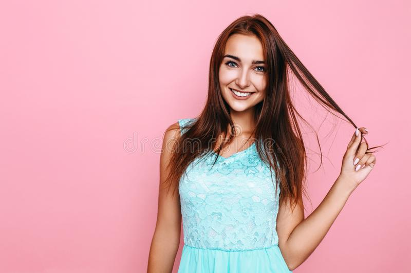 Young girl, in a bright dress, smiling and posing on a pink background. Portrait of an attractive girl in a bright dress holding a lock of hair and flirting on a royalty free stock photos