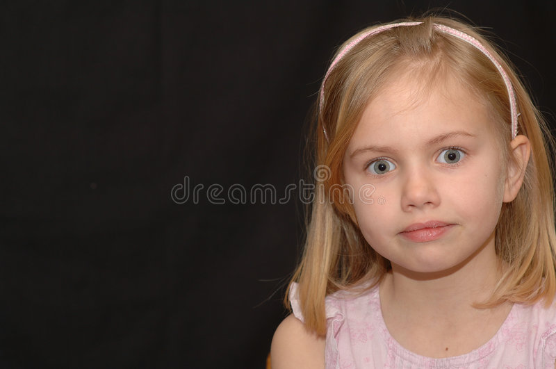 Young Girl With Bright Eyes. A great portrait of a cute 5-year old girl in a pink outfit with big, bright eyes royalty free stock image