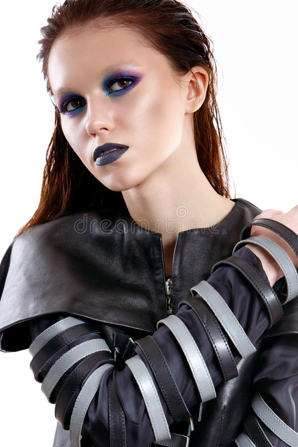 A young girl with a bright and bright makeup in the style of the gothic. Beautiful model with shining skin and in a leather suit royalty free stock images