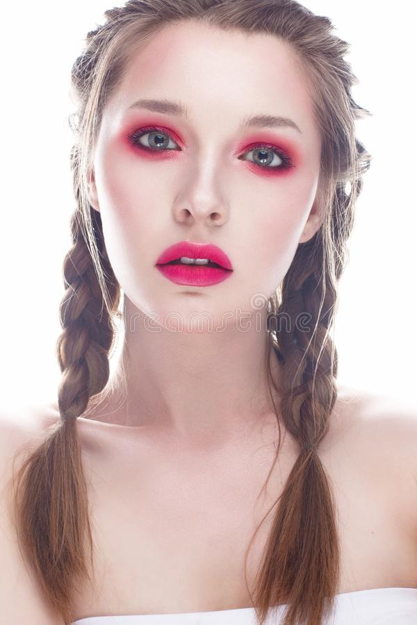 Young girl with bright pink creative make-up. A beautiful model with shining skin and braids. White isolated background. Beauty of. The face. Photo is taken in stock image