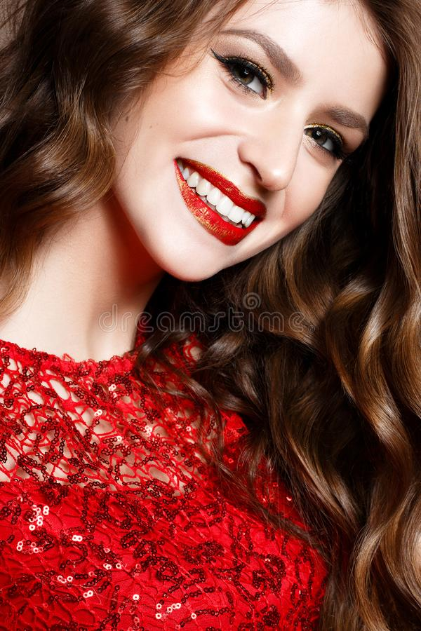 A young girl in a brilliant red dress and evening makeup. Beautiful smiling model in a New Year`s image with curls. Shining skin, stock image