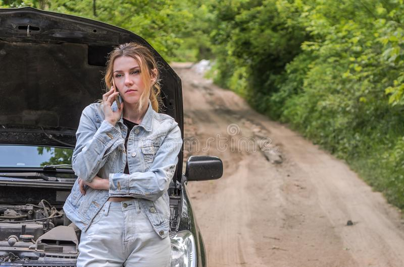 The young girl broke the car on the road, she opened the hood and called the phone calling for help to repair the car royalty free stock images