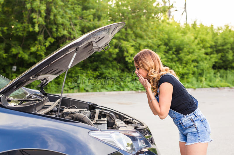 Young girl with broken down car and hood open call for help.  royalty free stock photography