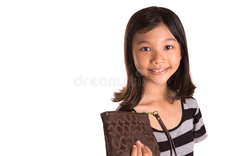 Young Girl With Brown Purse III. Young Asian Malay girl with a brown purse over white background royalty free stock images