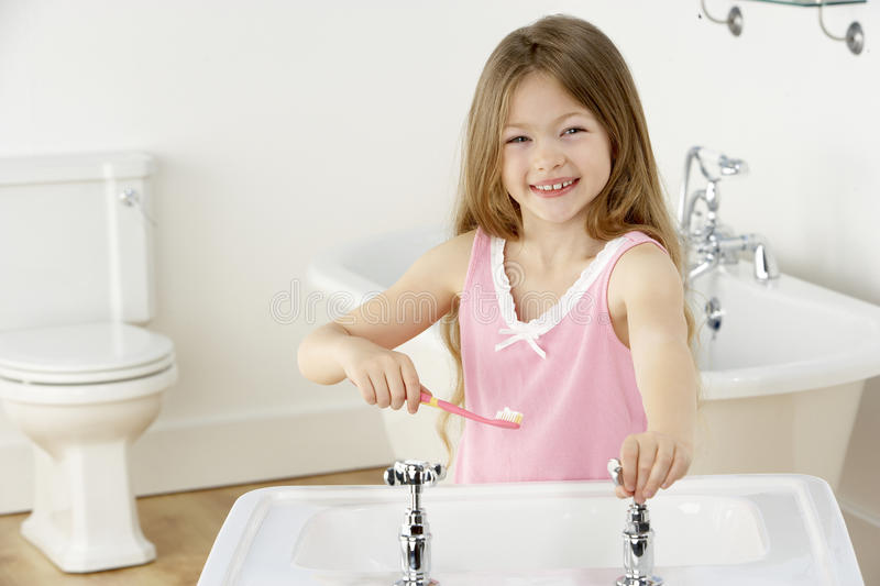 Young Girl Brushing Teeth at Sink. Pretty Young Girl Brushing Teeth at Sink royalty free stock photos
