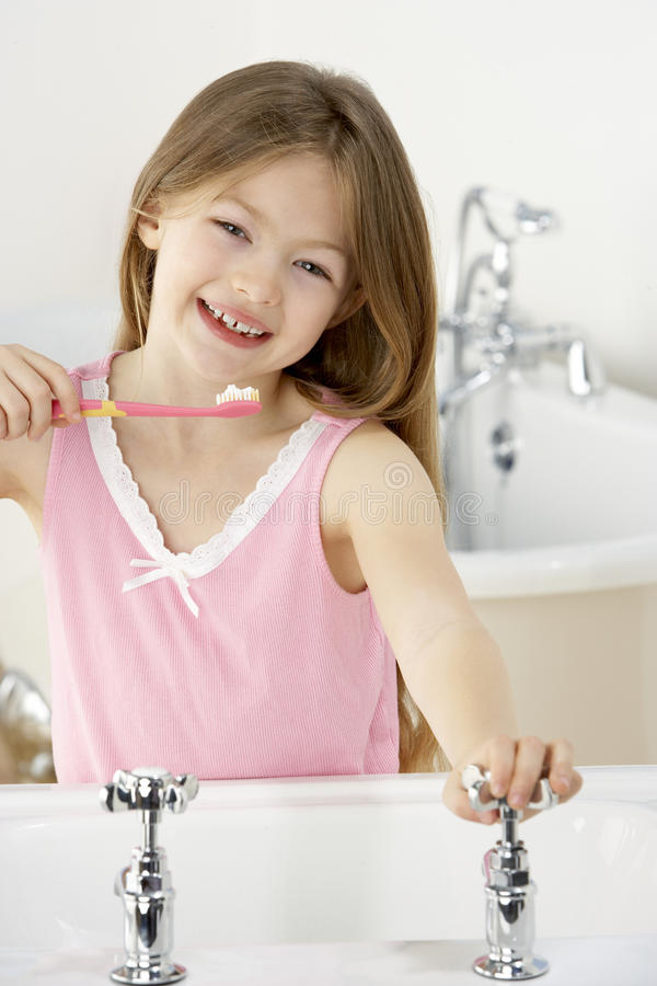 Young Girl Brushing Teeth at Sink. Turning The Tap stock photos