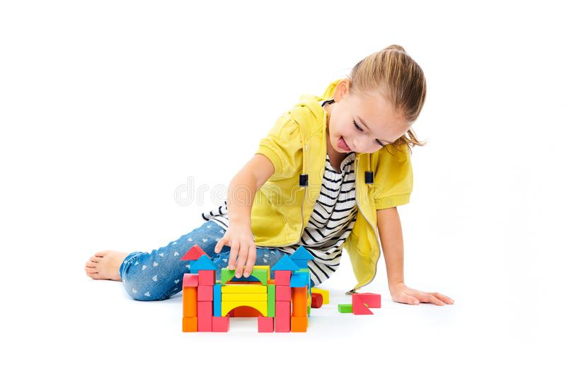 Young girl building a castle with wooden toy block. Child play therapy concept on white background. stock photos