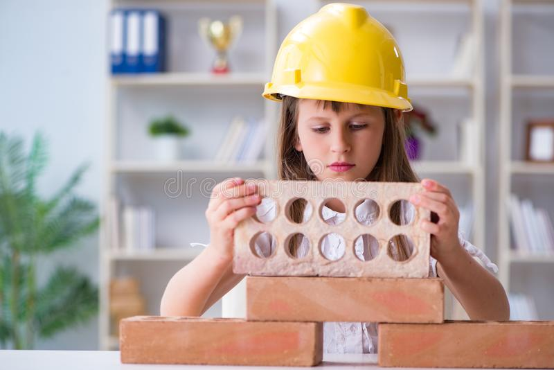 The young girl building with construction bricks royalty free stock images