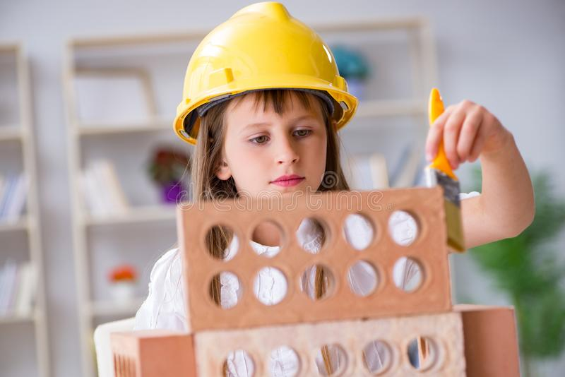 The young girl building with construction bricks stock images