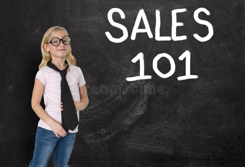 Young Girl, Businesswoman, Sales, Business, Marketing. A young businesswoman girl stands in front of a chalkboard with SALES 101 written on it. Can be used for royalty free stock images