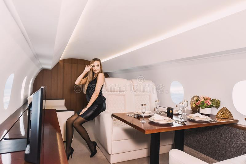 Young girl in the cabin of a business class airplane with a phone in her hands comfortable luxury travel royalty free stock images