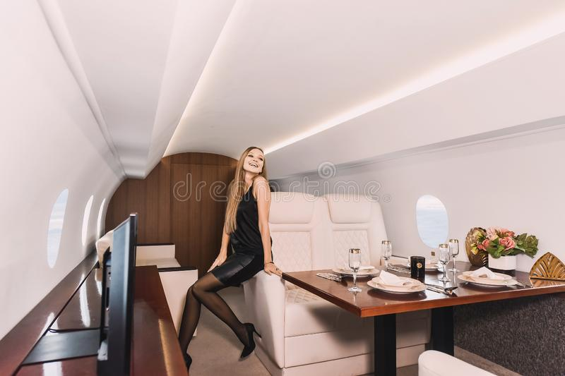 Young girl in the cabin of a business class airplane with a phone in her hands comfortable luxury travel stock images