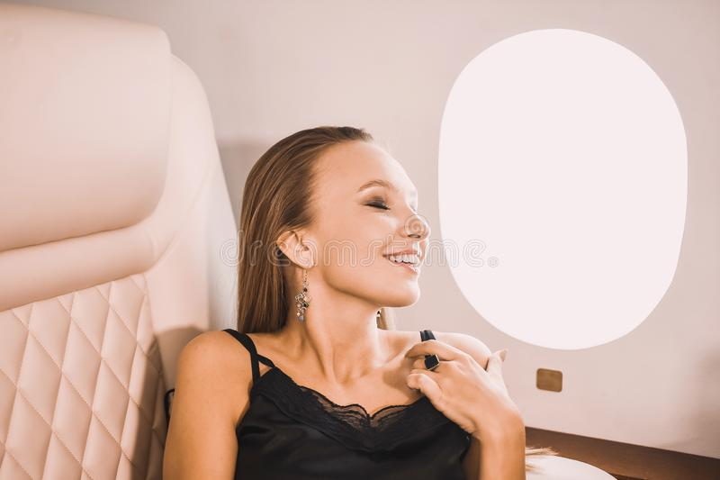Young girl in the cabin of a business class airplane with a phone in her hands comfortable luxury travel stock image
