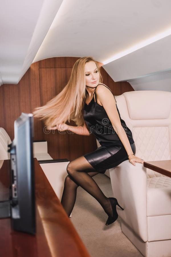 Young girl in the cabin of a business class airplane with a phone in her hands comfortable luxury travel royalty free stock photos
