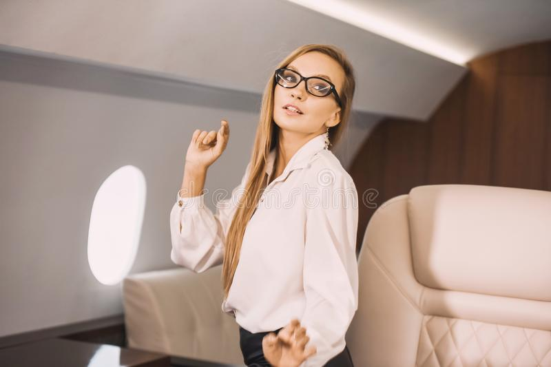 Young girl in the cabin of a business class airplane with a phone in her hands comfortable luxury travel stock photography
