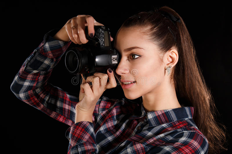 Young girl with a camera. Pretty young girl with a camera over black background stock photo
