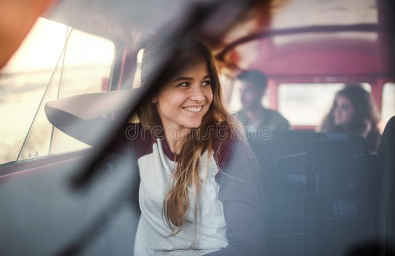 A young girl in a car on a roadtrip through countryside, shot through glass. royalty free stock image