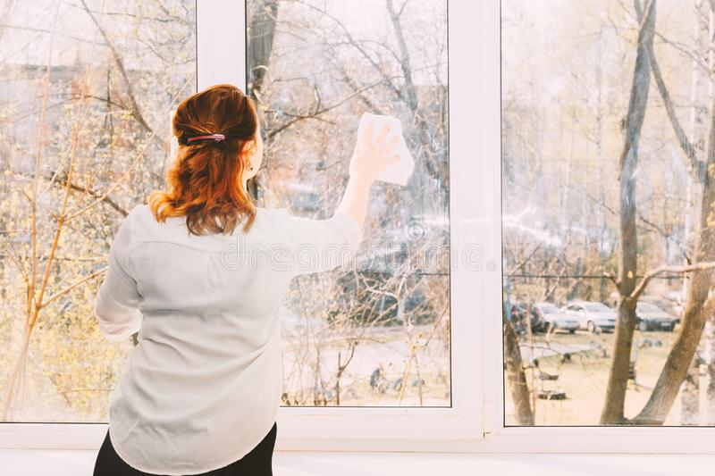 The young girl carefully washes and cleans a window royalty free stock photography