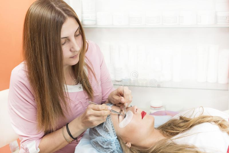 A young girl is carried out the correction of eyelashes in the beauty. Salon close-up royalty free stock photo