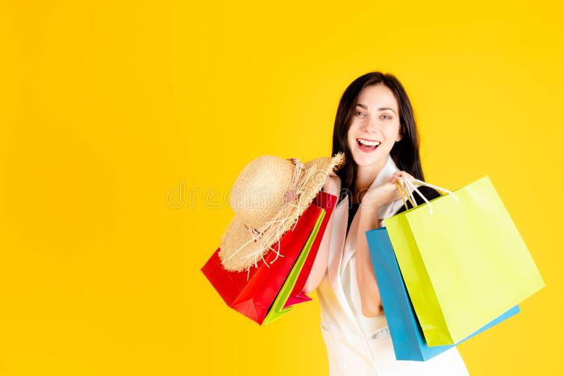 A young girl is carrying colorful shopping bags royalty free stock images