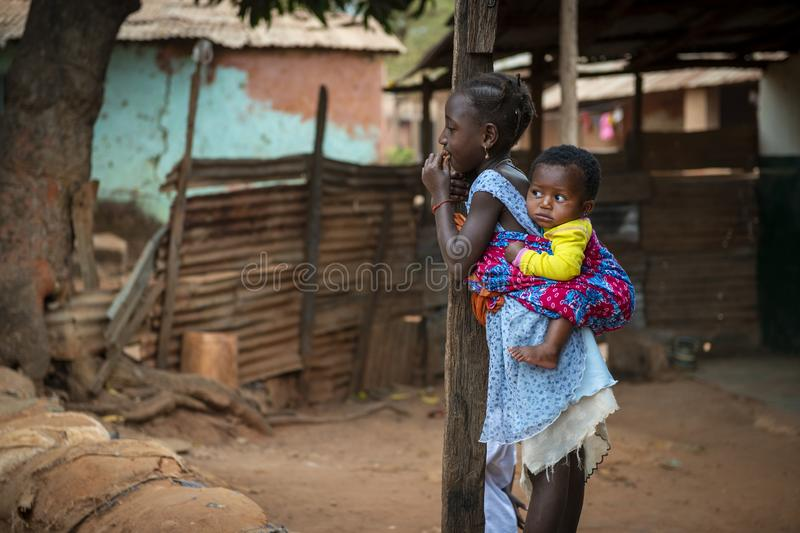 Young girl carrying her baby sister on her back at the Missira neighborhood in the city of Bissau. Bissau, Republic of Guinea-Bissau - February 6, 2018: Young royalty free stock photography