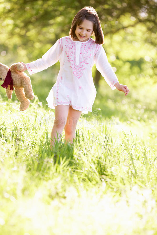 Young Girl Carrying Teddy Bear In Field Stock Photo
