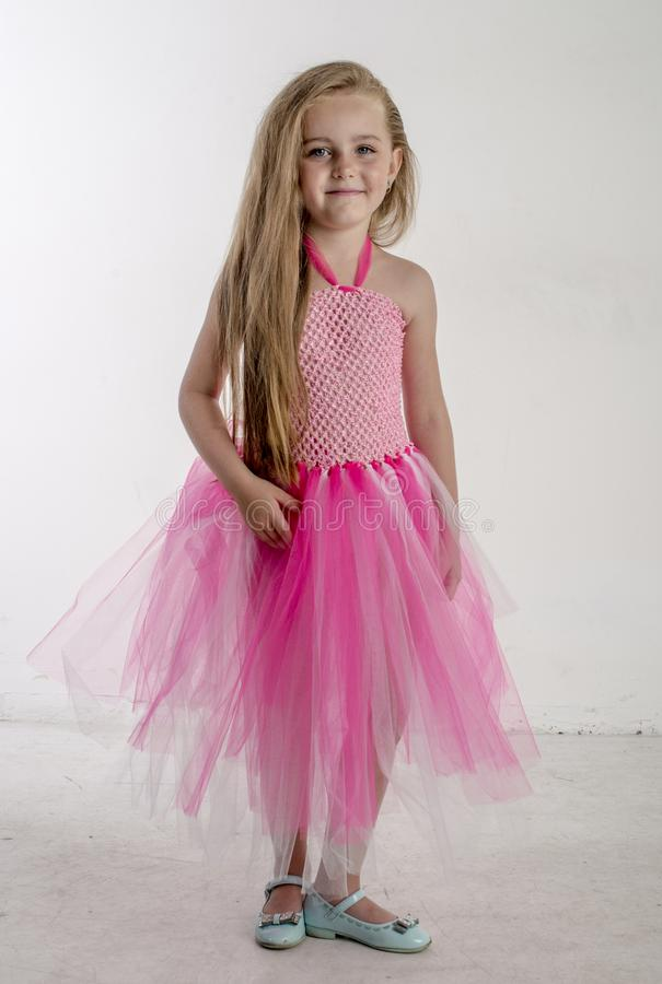 Young girl child in a pink festive dress with white blonde hair royalty free stock images