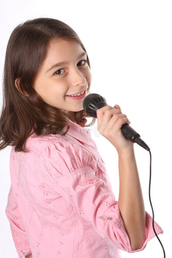 Young Girl / Child Singing in Microphone. Against white background royalty free stock image