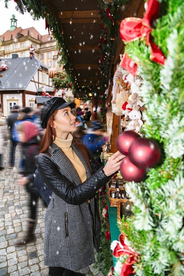 Young girl chooses Christmas tree at street fair royalty free stock image